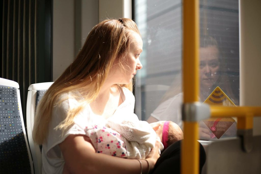 A white woman sitting on a tram looking out the window while she breastfeeds her daughter.